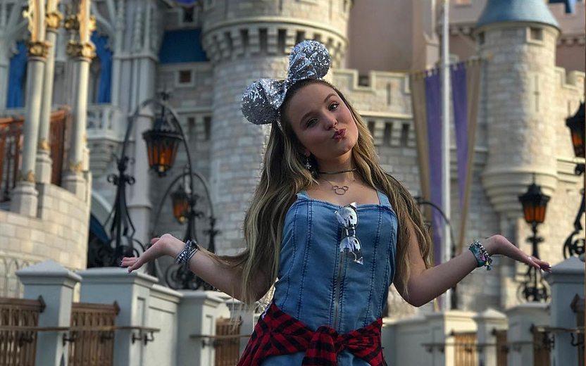 Larissa Manoela usa orelhas de mickey prateadas e posa em frente à castelo da Disney