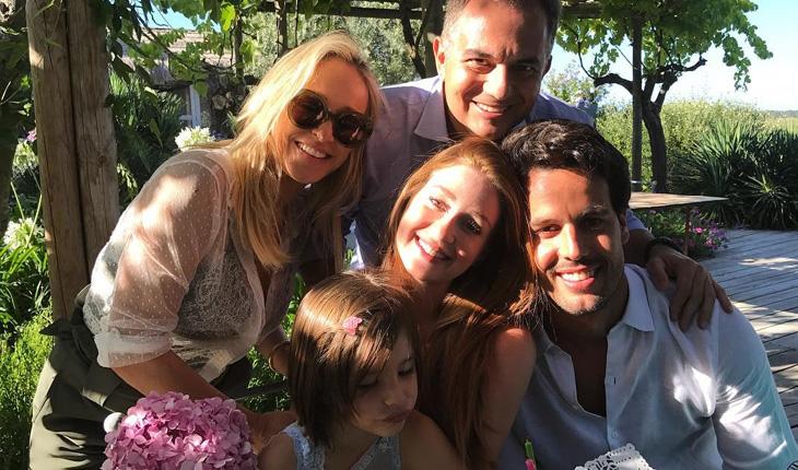 Casamento da Marina Ruy Barbosa: Marina e Xandinho sorriem em meio a familiares. Marina segura criança do colo