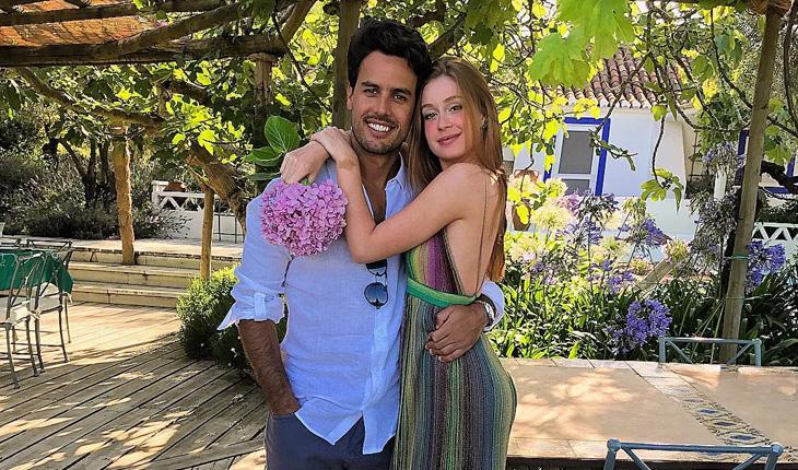 Casamento da Marina Ruy Barbosa: Marina usa vestido listrado em vende e segura buquê rosa enquanto abraça Xandinho, que usa bermuda e camisa branca