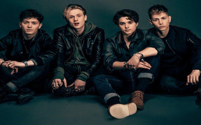 Integrantes da banda The Vamps sentados no chão com roupas escuras