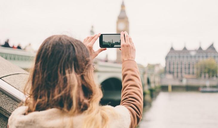 Moça fotografando a torre eiffel