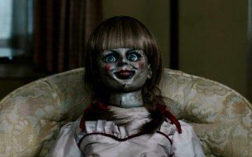 Boneca Annabelle sentada em sofá