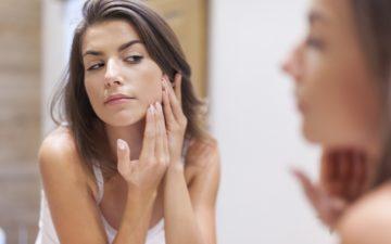 Menina olhando no espelho tentando evitar as espinhas