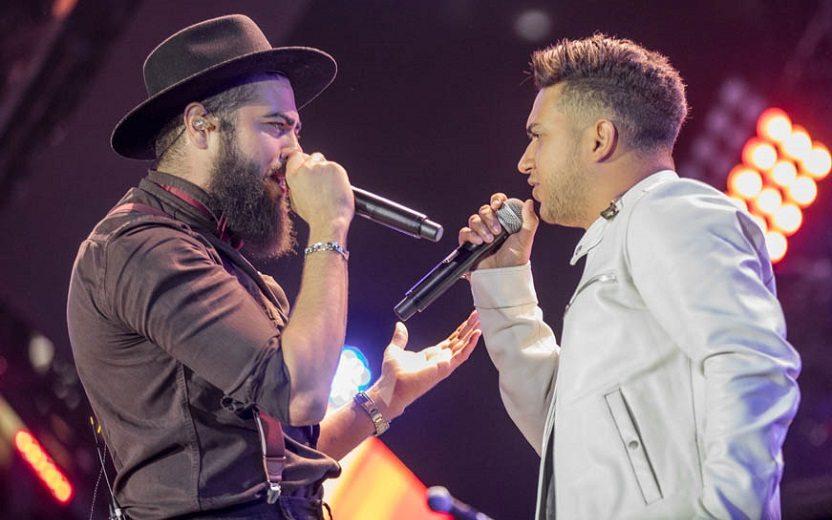 Henrique e Juliano de frente um para o outro durante um show cantando música do Henrique e Juliano