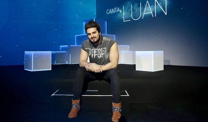 o cantor Luan Santana sentado em um puff com um letreiro