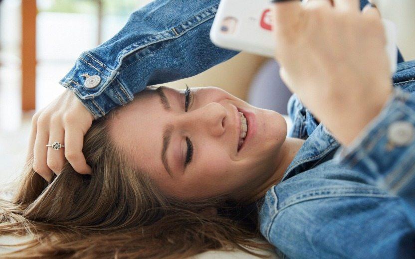 Valentina Schulz deitada, sorrindo ao ver o celular