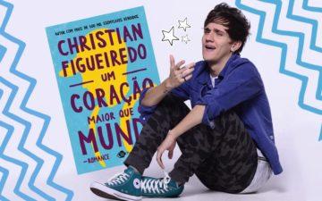 Christian sentado com seu novo livro ao lado