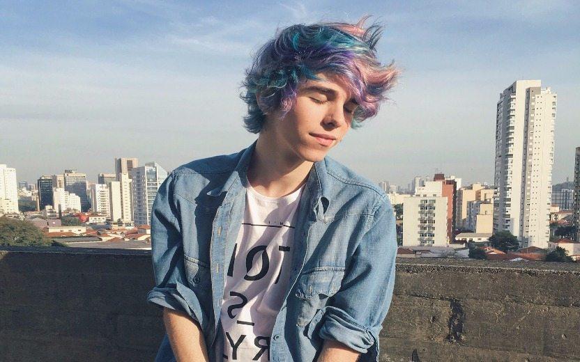 Erick Mafra, menino branco vestindo camisa jeans e de cabelo colorido, de olhos fechados com um fundo de céu e edifícios