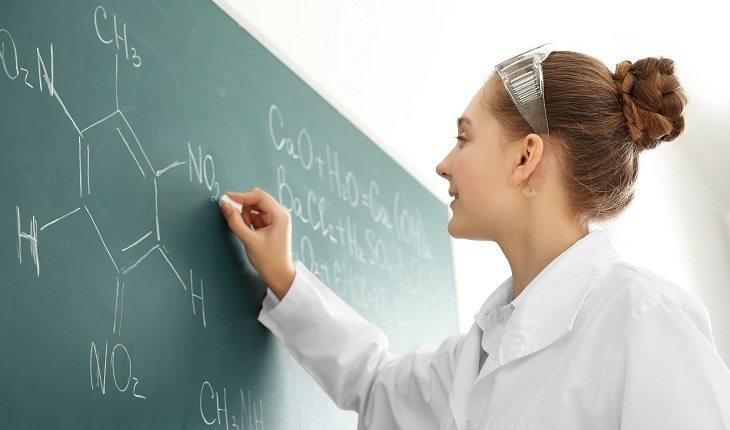 Menina escrevendo fórmulas na lousa
