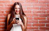 Menina sorrindo enquanto usa aplicativos no celular