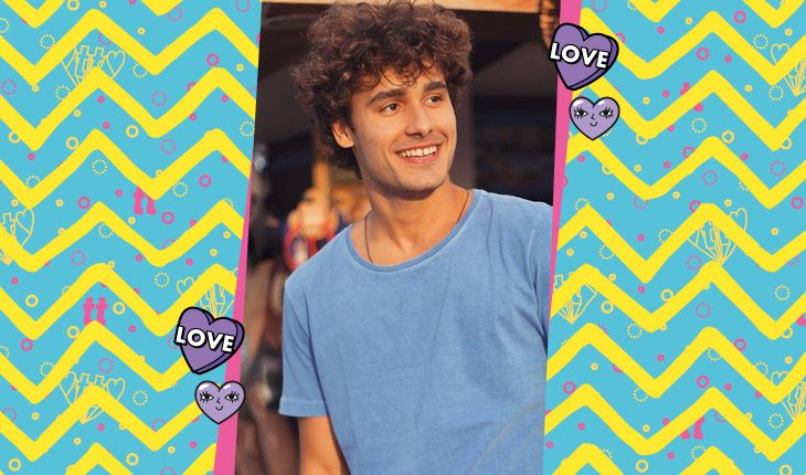 Bruno Peixoto de camiseta azul em pé e olhando para o lado