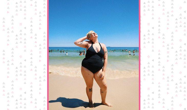 Luiza Junqueira na praia usando maiô preto
