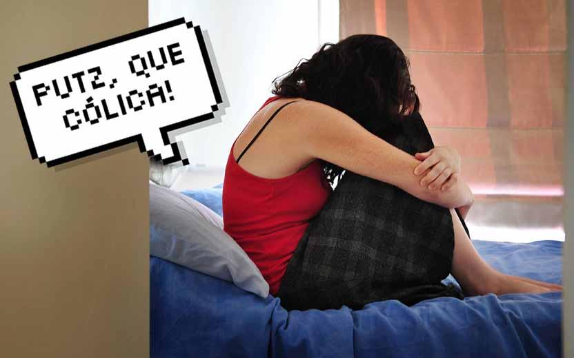 Menina sentada na cama sentindo cólica forte