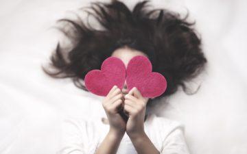 Menina com corações de EVA na mão para você descobrir como será seu Dia dos Namorados