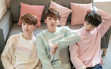 Meninos do grupo MONT sentados em frente a um sofá com almofadas