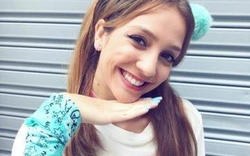 Denise TMJ com mão no rosto e sorrindo