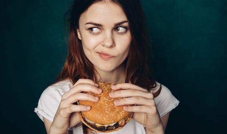 menina olhando para o lado com hamburguer na mão
