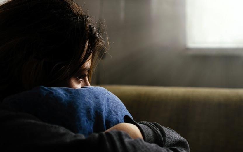 Suicídio na adolescência - Menina sentada segurando a perna com cara de sofrimento