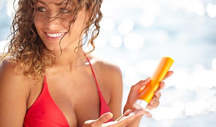 Garota de biquíni passando protetor solar
