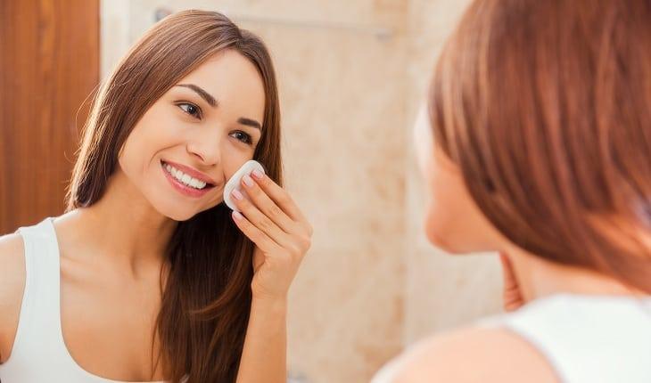Garota tirando maquiagem e limpando a pele