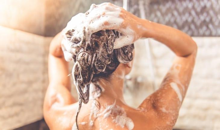 Garota tomando banho com água quente e lavando o cabelo