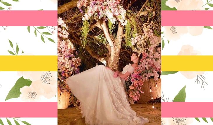 Camila Queiroz sentada no balanço de flores