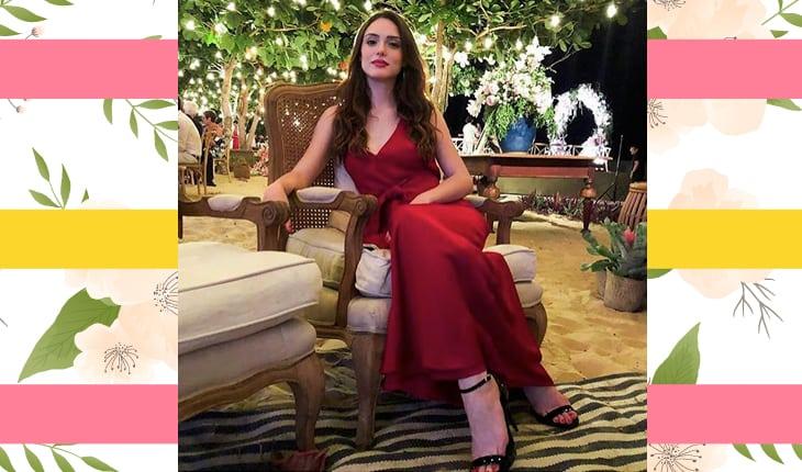 Isabelle Drummond com vestido vermelho sentada