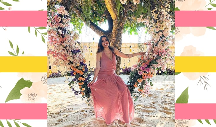 Taciele Alcolea sentada em balanço de flores