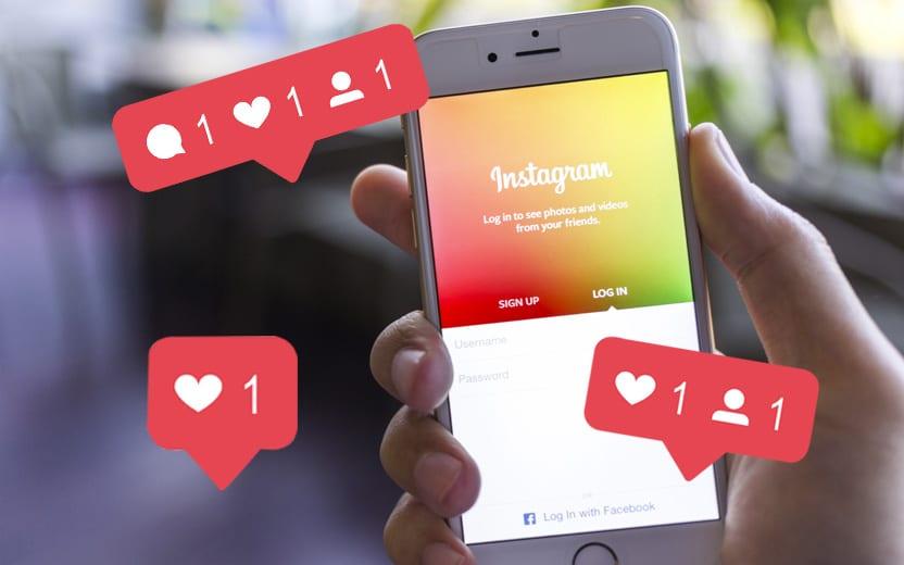 Mão segurando um celular com o Instagram aberto - Insta fake