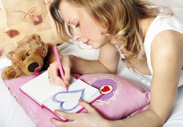 menina desenhando um coração no caderno