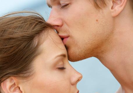 Homem beijando testa de mulher
