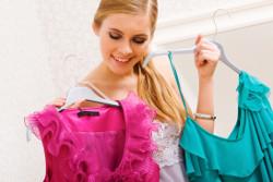 Menina segurando cabides com roupas